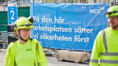 "Two workers in the foreground. The text in the background says ""at this workplace, we put safety first"". Foto/illustration: Joakim Kröger"
